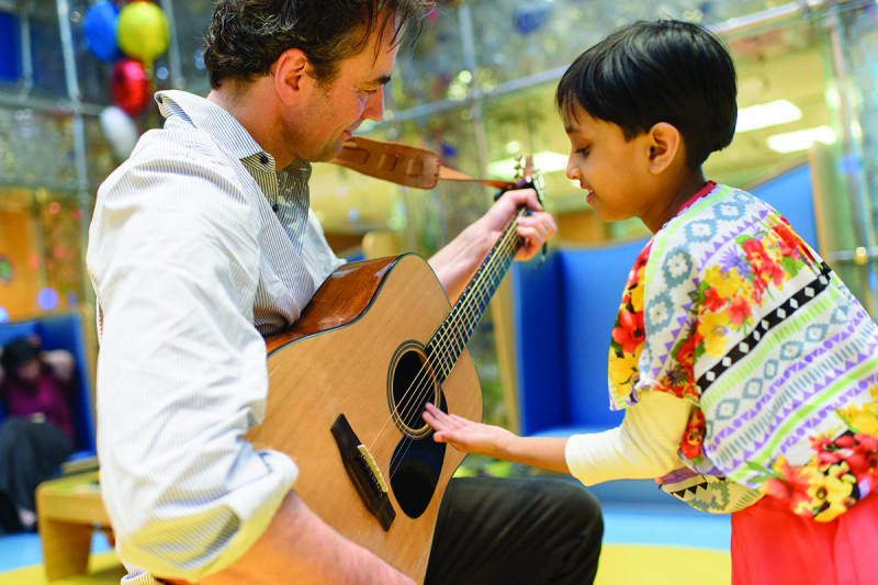 Man playing guitar while child watches