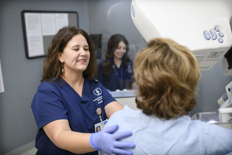 A woman receives a mammogram, and two technicians help her.
