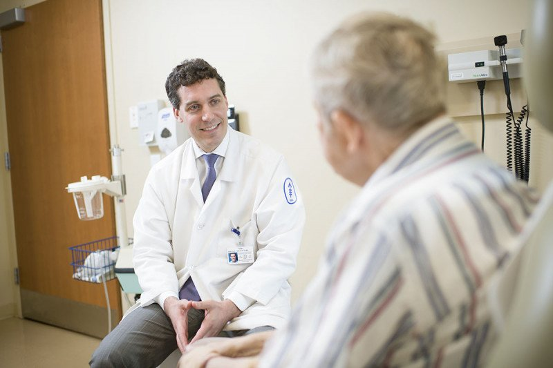 Medical oncologist Michael Postow with a patient