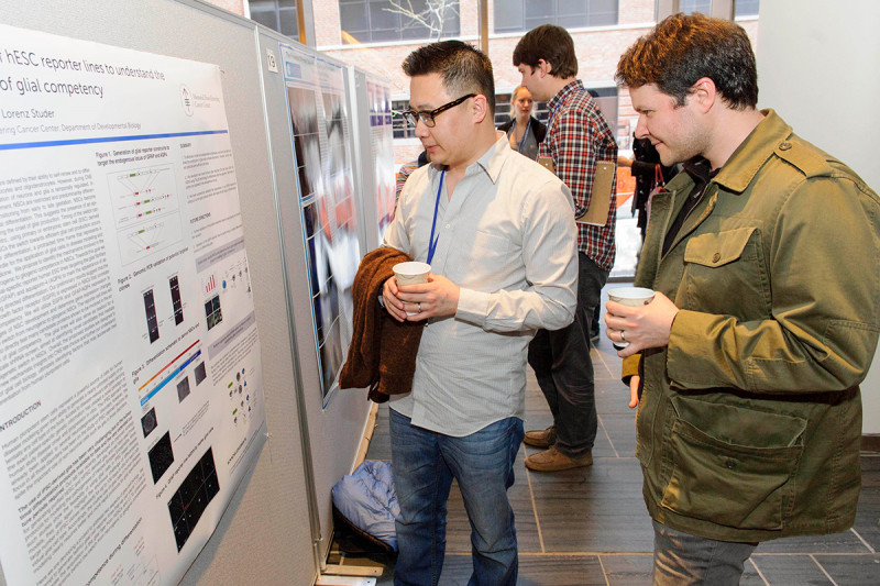 Stuart Chambers (right) of the Sloan Kettering Institute's Developmental Biology Program discussing work at the poster session and reception.