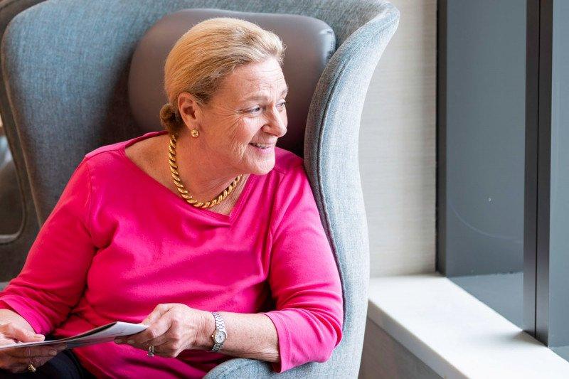Mujer con blusa rosa, sentada mirando por una ventana