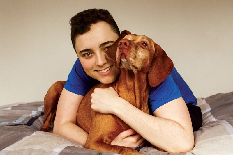 A teenage boy hugs his dog