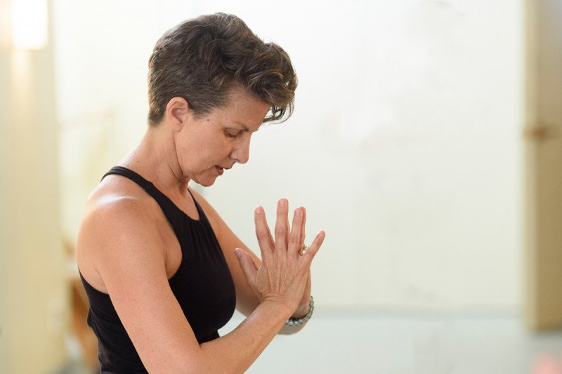 A woman in exercise clothing bows her head with her hands together at her heart.