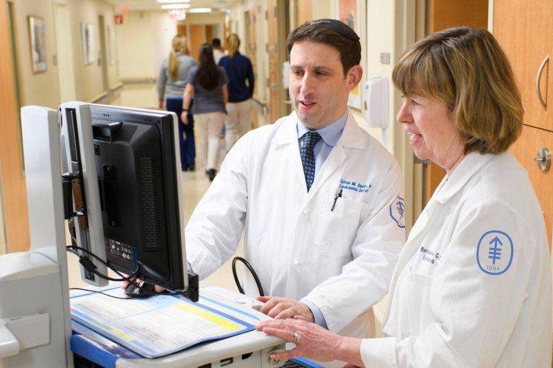Eytan Stein at a computer with nurse practitioner Bernadette Cuello