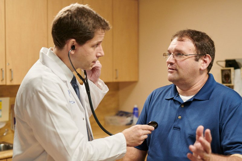 Medical oncologist William Tap speaks with a patient.