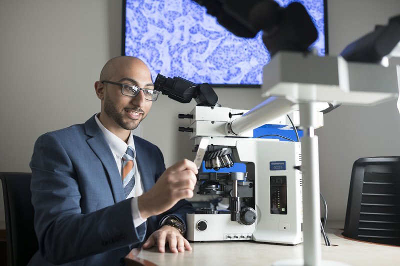 Pathologist Matthew Hanna in front of a microscope