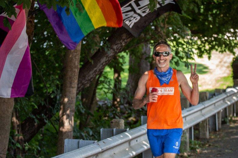 Sandy wearing an orange tank top and running.