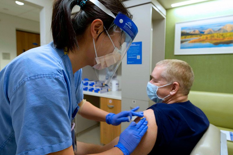 Jian Wu, RN, gives a COVID-19 vaccine to Timothy Evans, pulmonary function technologist.
