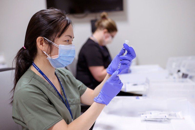 Сотрудник медицинского учреждения готовит вакцину