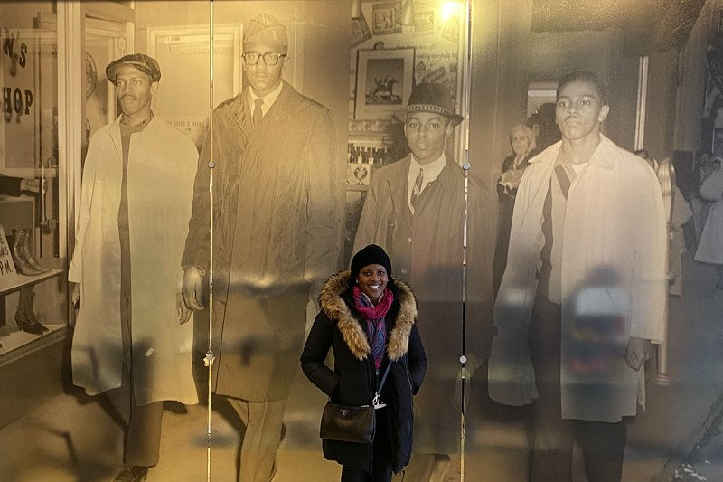 MSK's Dr. Melody Smith in front of a photograph of the Greensboro Four