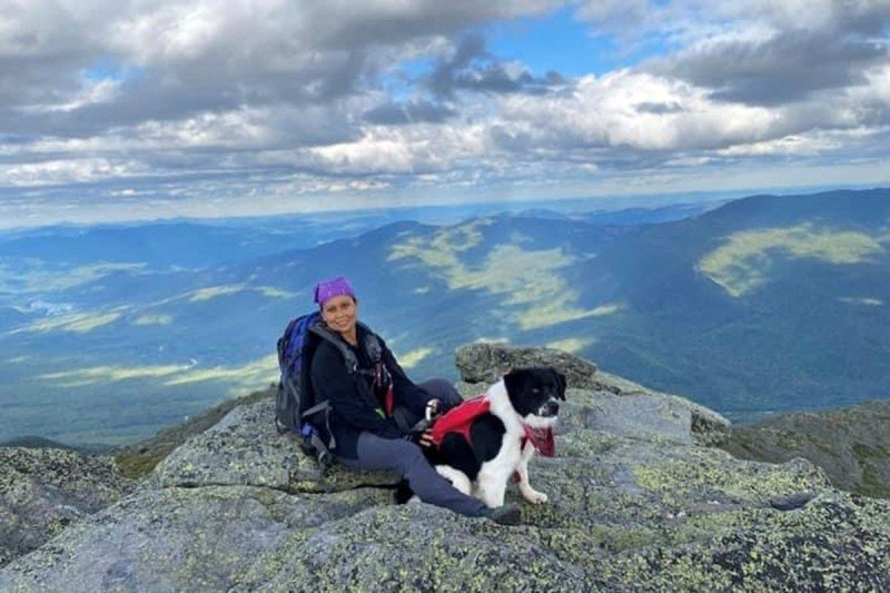 Elaine sitting down on a mountain with her border collie between her legs