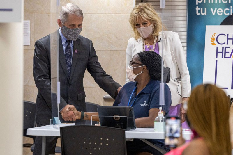 Anthony Fauci shakes hands with Shakima Grant as Dr. Jill Biden looks on