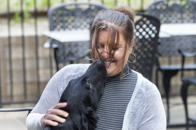 Patient Courtney Diana receiving doggie kisses from Plum