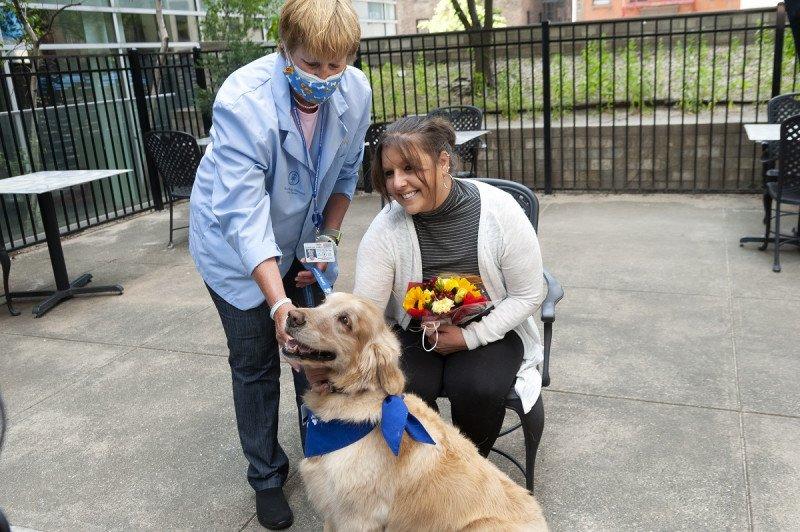 Volunteer Karen Koehler (left) and her Caring Canine CJ reuniting with patient Courtney Diana