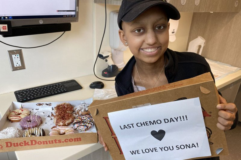 """Sona posing with a box of donuts that says """"Last chemo day! We love you, Sona!"""""""