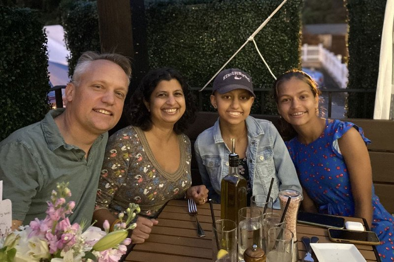 Sona with three family members at a dinner table