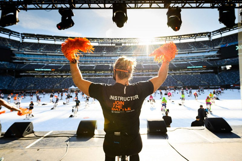 Woman with two pom poms on stage at the Cycle for Survival event at MetLife Stadium