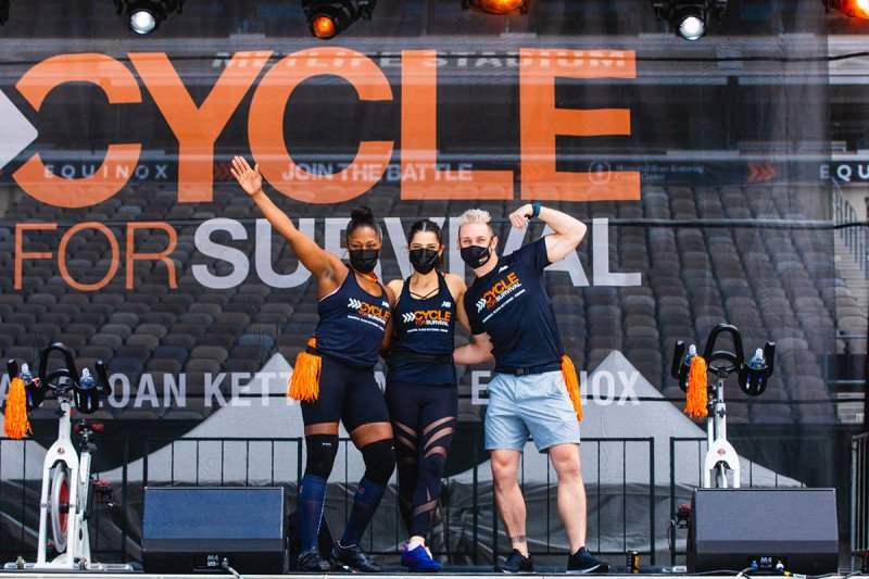 Three people on stage at the Cycle for Survival event at MetLife Stadium