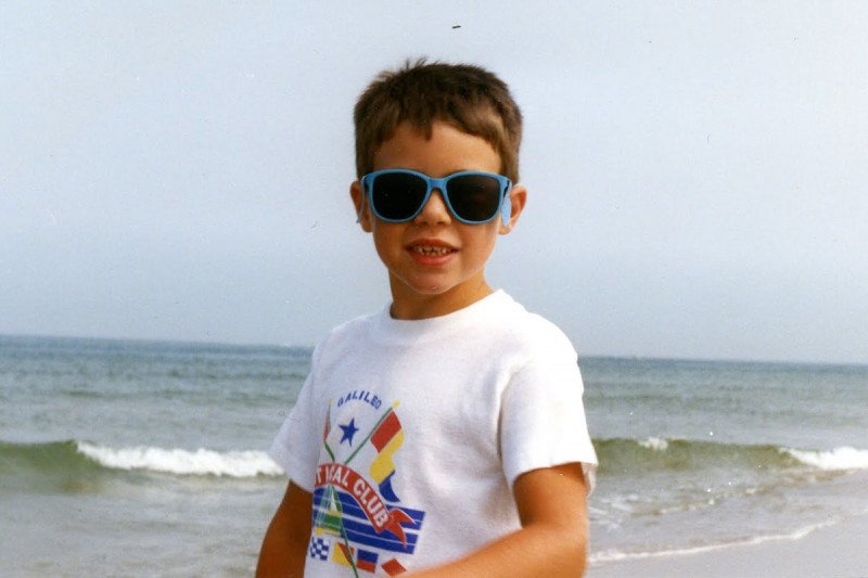 Young Ben wearing sunglasses at the beach.