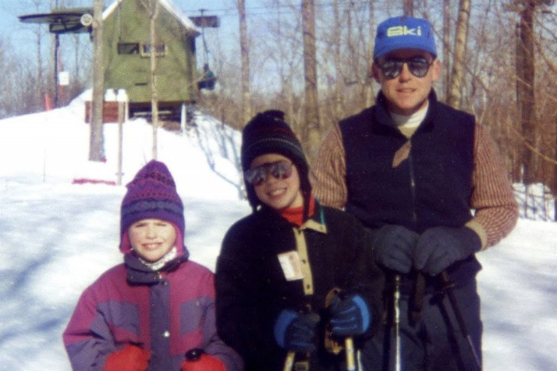 Two children with their dad, standing in snow.