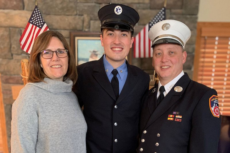 Woman pictured with son in EMT uniform and husband in firefighter uniform.