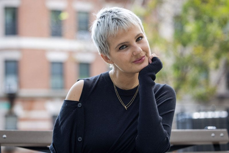Young woman with short hair poses for photo