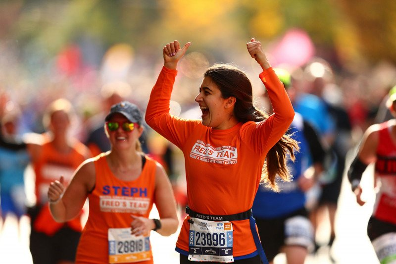 Two Fred's Team runners wearing orange shirts in a crowd