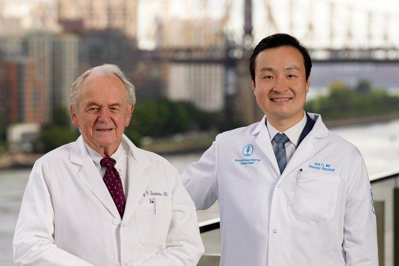 Sir Murray Brennan and Bob Li wearing white coats and posing for a photo outside