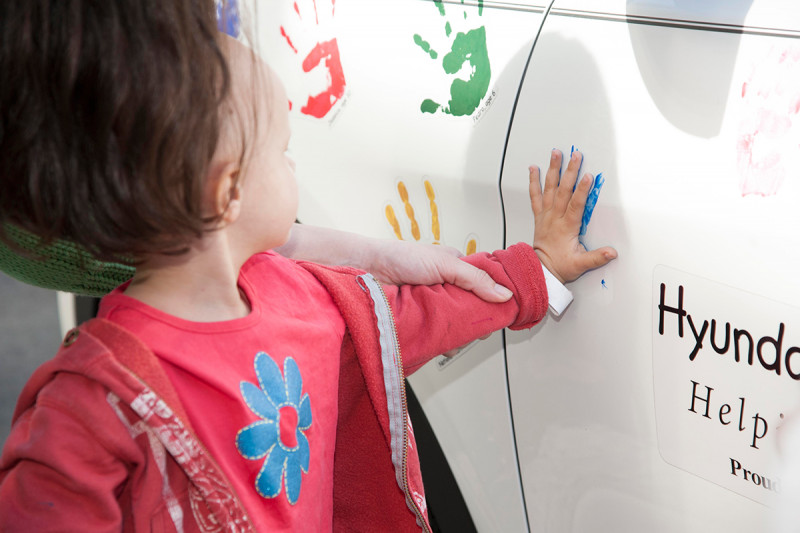 Scarlett, 3, leaves her handprint on the Hyundai Hope on Wheels car.