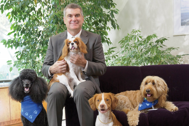 Memorial Sloan Kettering President Craig Thompson receives canine therapy.
