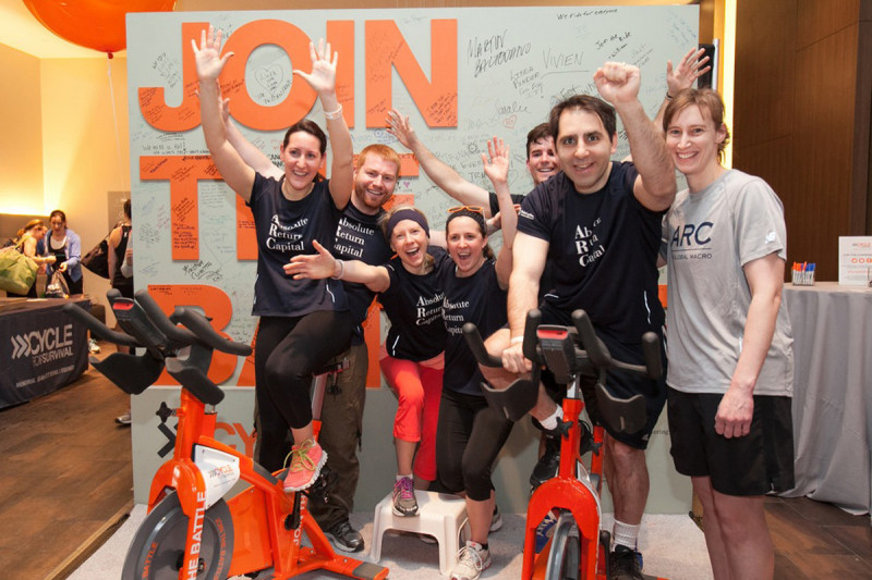 Riders in Boston take a photo on the battle bike. Participants sign the wall behind the battle bike to declare their commitment to beating rare cancers.