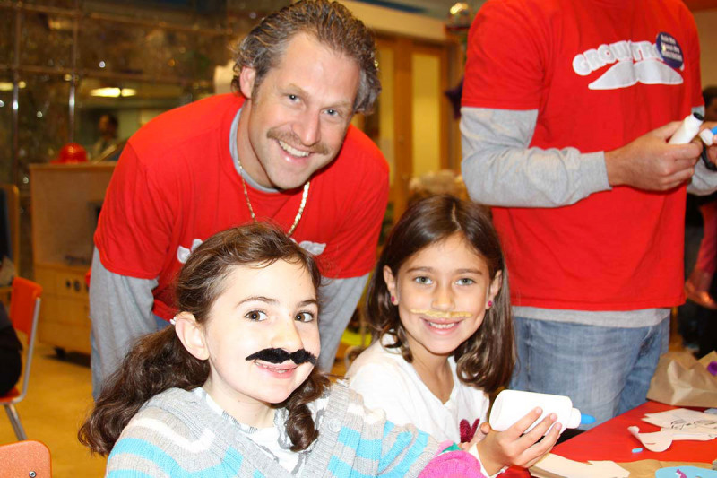 Grace O. and Rileigh, pictured with a volunteer from Mustaches for Kids, prove the mustache fun isn't just for the boys (or men).