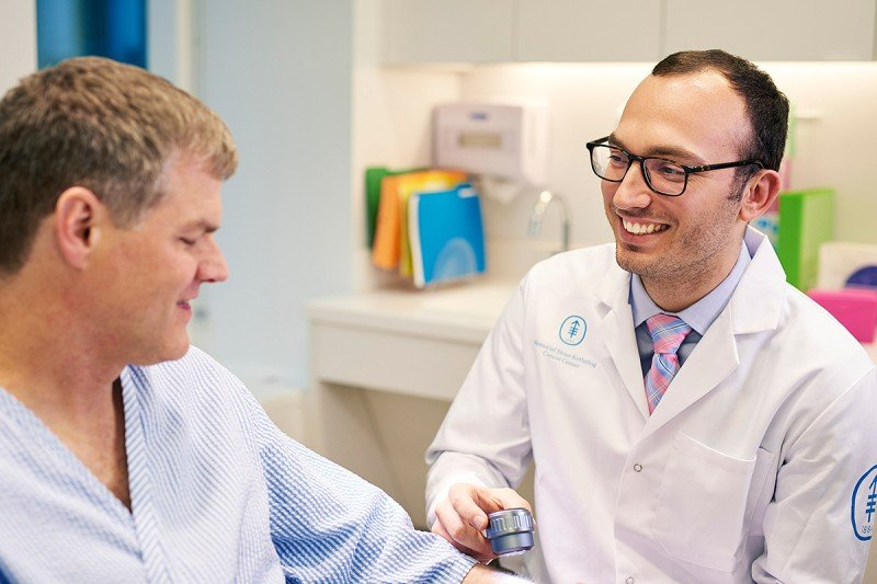 Dermatologist Michael Marchetti speaks with a patient about treatment options for melanoma.