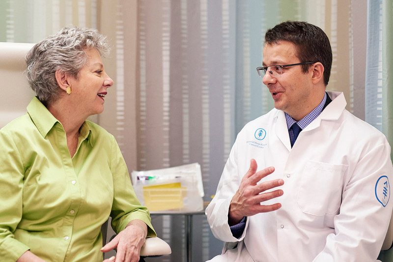 A surgeon speaks with a patient.