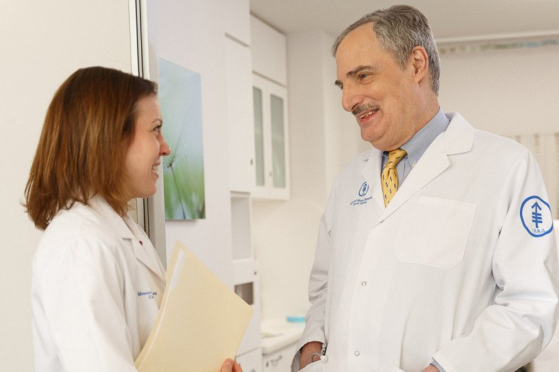 MSK hematologic oncologists, David Straus, dressed in a white coat speaks to a female nurse holding a folder.
