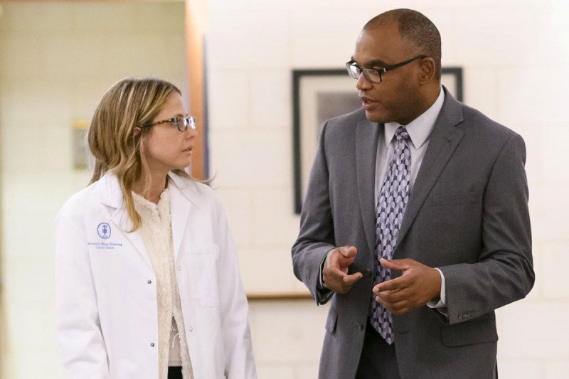 Female doctor in a white coat walking with a male doctor wearing a suit