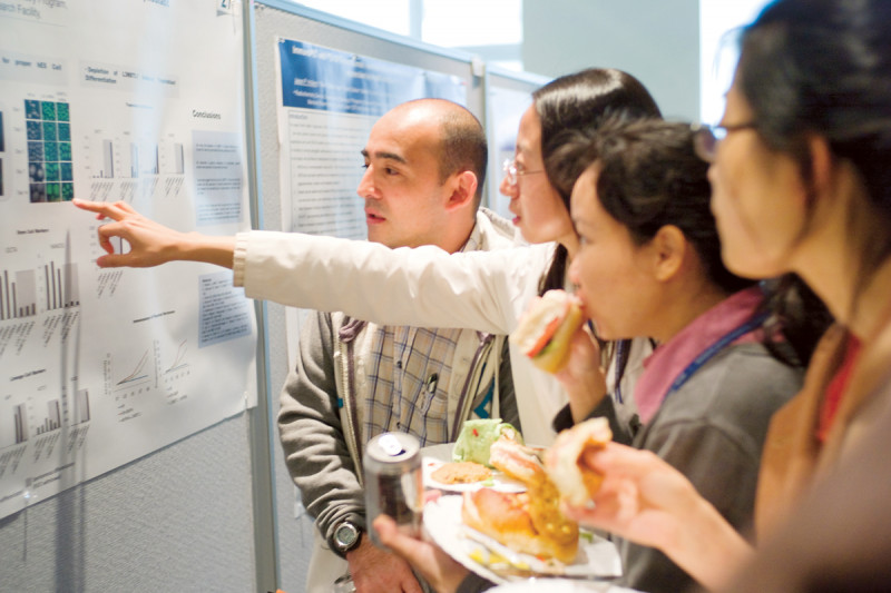 Postdoctoral researchers discuss a poster presentation