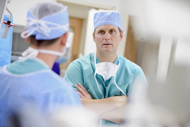 MSK pancreatic and liver cancer surgeon, Peter Allen, speaks with fellow colleagues dressed in their scrubs.