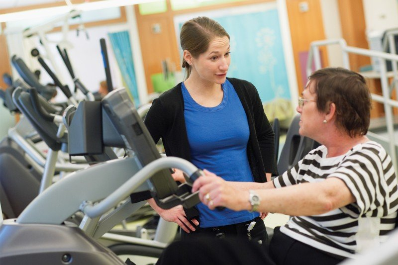 Physical therapist Tiffany Kendig guides a patient in strengthening her lower body.
