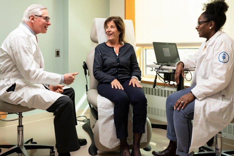 Un médico y una enfermera en una sala de exploración con una paciente