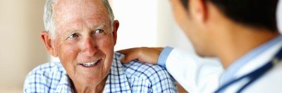 An older man in a checkered shirt smiles at his doctor, who has his hand on the man's shoulder.