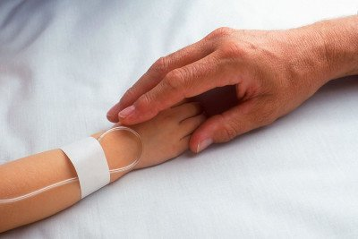 Child hand with IV holding adult hand.