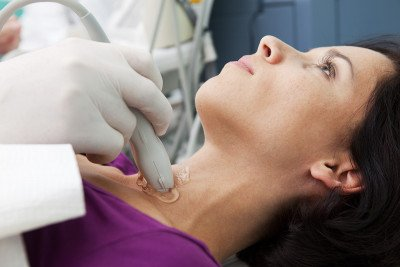 Woman lying back receiving ultrasound on neck.