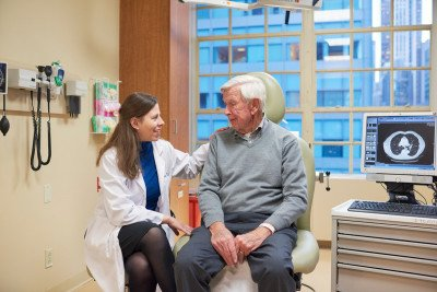 A young female doctor in a white coat sits with an older male patient in an exam room