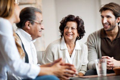 Photo of four people around a table smiling and conversing.