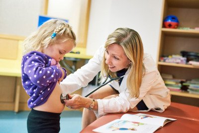 Pediatric radiation oncologist Suzanne Wolden examines a young patient.