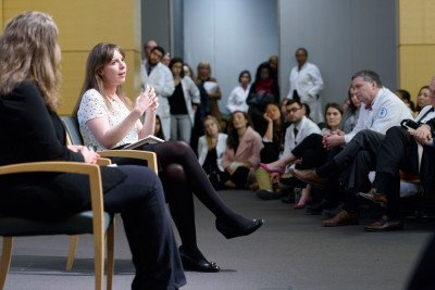 Lucy Kalanithi gestures while speaking. Physicians in white lab coats look on.