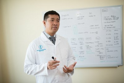 Physician standing in front of a whiteboard