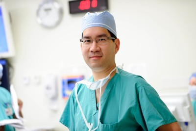 Doctor in green surgical scrubs wearing glasses and cap looking at camera.