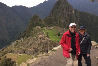 Husband and wife standing on a mountain at Machu Picchu in Peru, with the citadel in the background